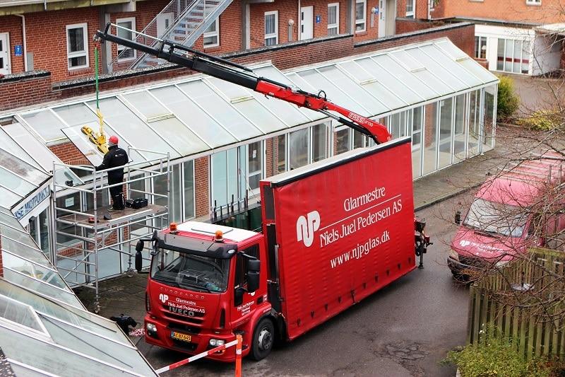 Lastbil med kran og sug monterer vinduesglas på mål. njpglas.dk
